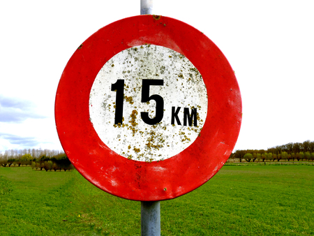 city limit: old dirty 15 km per hour speed sign with meadow background Stock Photo