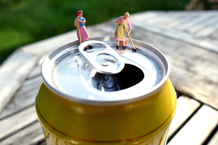 lata de refresco: mujeres de la limpieza en miniatura de barrido en la parte superior de la lata de refresco con el fondo borroso. Concepto de negocio Foto de archivo