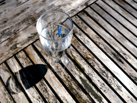 head down: Miniature workmen floating head down in champagne glass outside on wooden table. Business concept