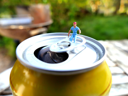 lata de refresco: obrero en miniatura que se sienta encima de la lata de refresco con el fondo borroso. Concepto de negocio