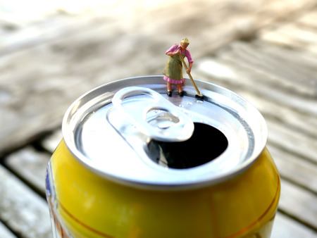 lata de refresco: Miniatura se�ora de la limpieza barriendo en la parte superior de la lata de refresco con el fondo borroso. Concepto de negocio
