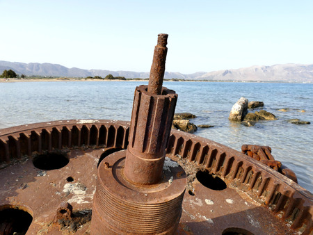 interlink: Detail of rusted cogwheel of old ship stranded on beach, close up