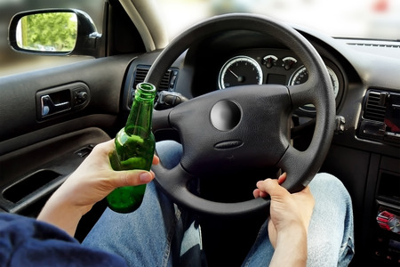 Unrecognizable man drinking and driving. Dangerous driving concept. Imagens