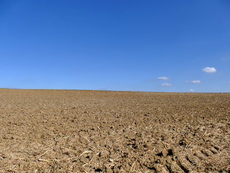 arando: Cultivated ploughed field under blue sky and some clouds Foto de archivo