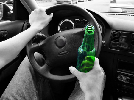 irresponsible: Unrecognizable man drinking and driving. Black and white. Focus on bottle in color. Dangerous driving concept.