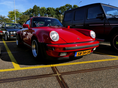 Amsterdam, The Netherlands - September 10, 2016: Red Porsche 911 Turbo 1983 on display during Cars & Coffee XXL show. Non-ticketed public event held in the streets of the city with people carspotting.