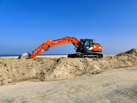 Orange excavator on pile of sand near the beach