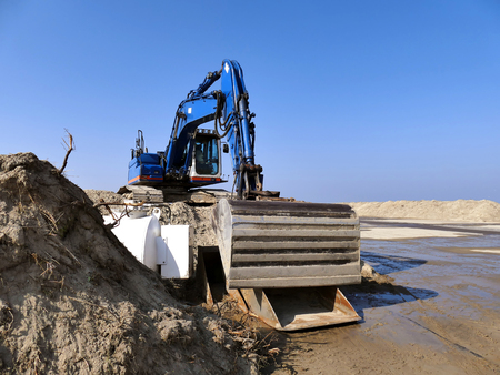 undercarriage: Blue excavator on pile of sand on construction site