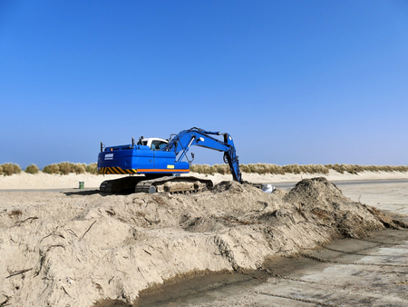 Blue excavator on pile of sand at empty road Stock Photo