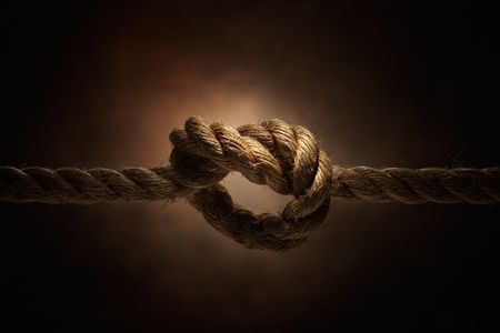 locking up: rope tie into a knot, studio shot Stock Photo