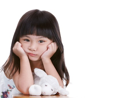 sad child: not a happy little girl, white background Stock Photo