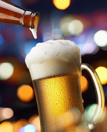 cerveza: jarro de cerveza en m�s de flujo con luces de colores Foto de archivo