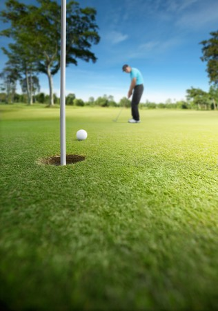 putting green: golfer putting at golf course, shallow depth of field Stock Photo