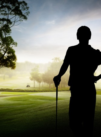 silhouette of a golfer standing by the course