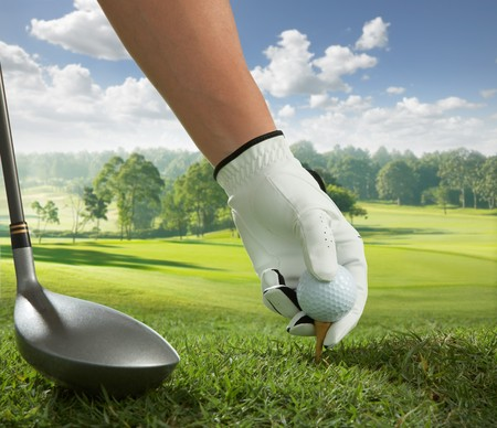 hand placing a tee with golf ball photo