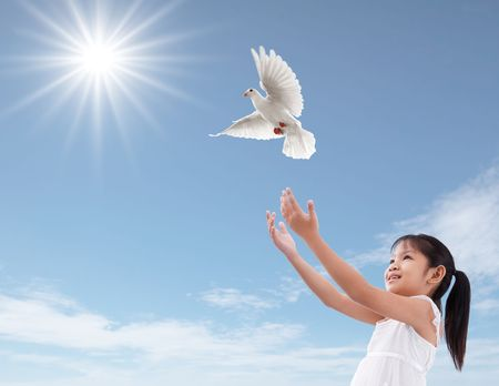 cheerful young girl releasing a white dove