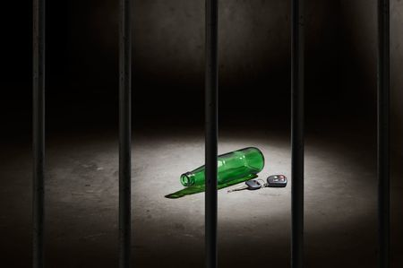 drink and drive: empty beer bottle and car key behind bars, dont drink and drive concept Stock Photo
