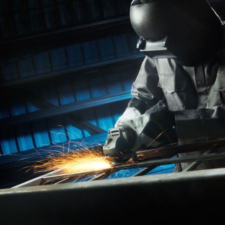 grinding: man grinding in workshop with safety precaution Stock Photo