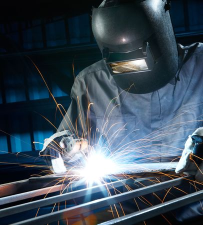 welding metal: man welding with reflection of sparks on visor