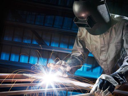 welding metal: man welding in workshop with safety precaution