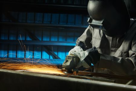 man grinding in workshop with safety precaution photo