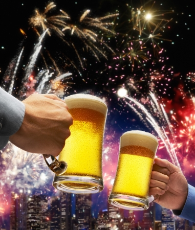 beer toasting with firework and skyline as background photo