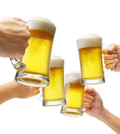 vasos de cerveza: cuatro manos sosteniendo cervezas hacer un brindis