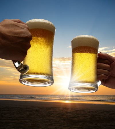 hands holding beers toasting on beach at sunset photo