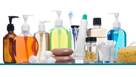 various personal hygiene products on glass shelf photo