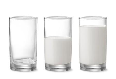 nutrientes: tres vasos mostrando cada vez mayor cantidad de leche  Foto de archivo