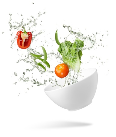 various type of fresh vegetables splashing out from spilling bowl photo