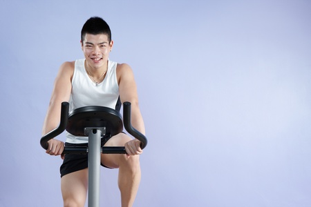 asian man cycling on exercise bike with copy space photo