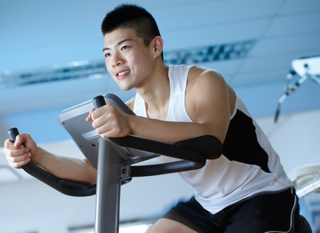 asian man cycling on exercise bike in gym Stock Photo - 9833255