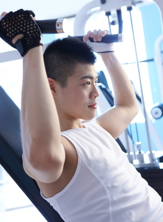 asian man workout in gym using exercise machine Stock Photo - 10080956