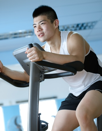 asian man cycling on exercise bike in gym Stock Photo - 10080959