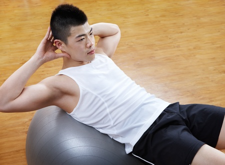 asian sport: asian man doing sit up on fitness ball