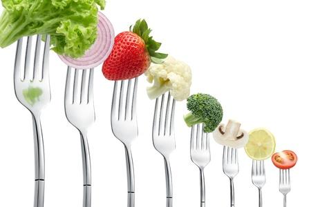 alimentos saludables: horquillas con verduras en una fila aislados en blanco