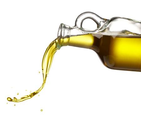 gieten olijfolie uit glazen fles tegen een witte achtergrond Stockfoto