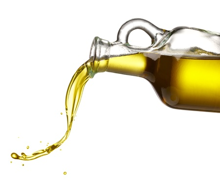 pouring olive oil from glass bottle against white background Foto de archivo