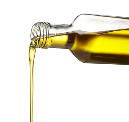 cooking oil: pouring olive oil from glass bottle against white background Stock Photo