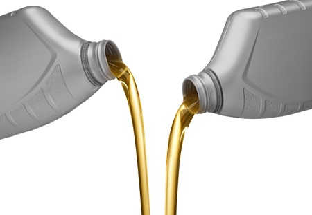 oil change: two bottles of engine oil being poured Stock Photo