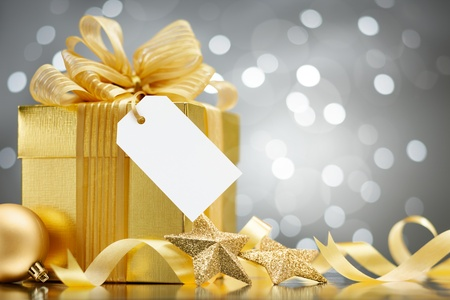gift tag: christmas gift with blank tag against bokeh lights background Stock Photo