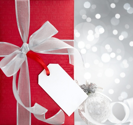 christmas gift with blank tag against bokeh lights background photo