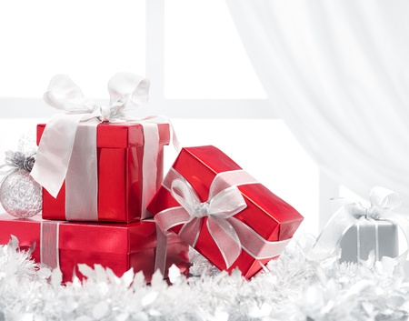 christmas gifts and ornaments against window with curtain photo
