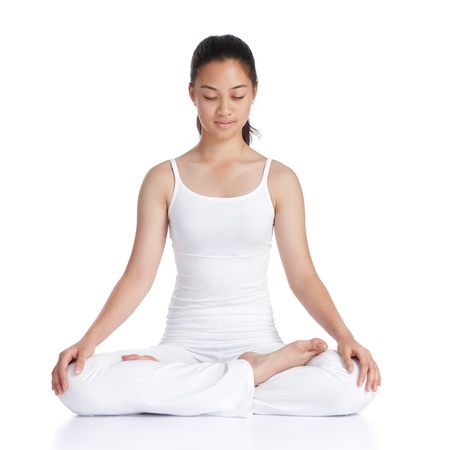 female asian teenager doing meditation against white background photo