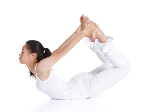 dhanurasana: female asian teenager doing yoga against white background