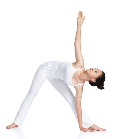 trikonasana: female asian teenager doing yoga against white background