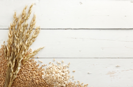 unprocessed: oats with its processed and unprocessed grains against white wood background Stock Photo