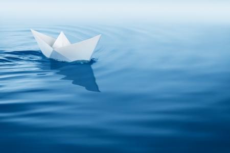 papier boot varen op de blauwe wateroppervlak Stockfoto
