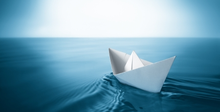 sail boat: origami paper sailboat sailing on blue water Stock Photo